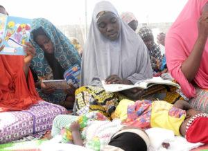 Hau'wa reads and watches over her twin daughters at a non-formal learning center in northern Nigeria