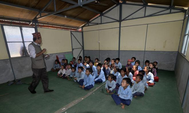 Photo: Headmaster Sitalal Tamang interacts with students in one of the new classrooms built by USAID and UNICEF.