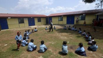 Photo: Headmaster Sitalal Tamang, center, plays educational games with students in the schoolyard.